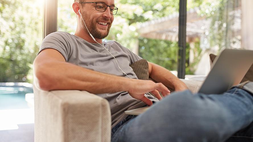 screenshot van een man in een t-shirt, een baardje en een bril, die in een luie stoel zit met een laptop op zijn schoot
