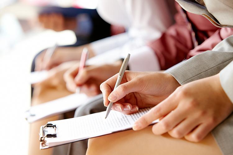 closeup van 3 mensen die een pen en notitieblok vasthouden en hard aan het werk zijn